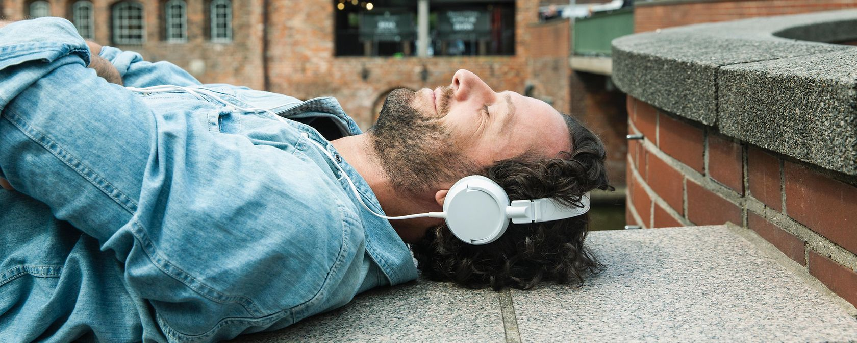 kopfhoerer-musik-mann-liegen-entspannung-outdoor-gettyimages-589935801